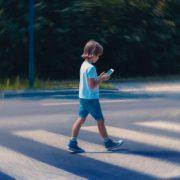 Dziecko ze smartfonem na przejściu dla pieszych